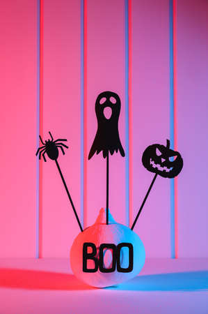 Halloween home decorations. Painted white pumpkin and black scary Halloween puppets on sticks, illuminated with neon light. Copy space, vertical orientation. Stock Photo