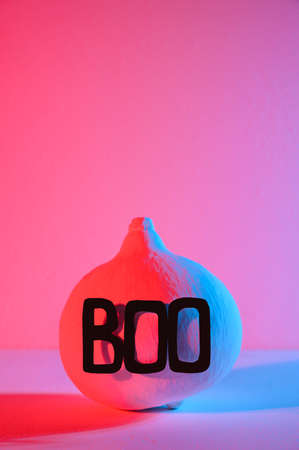 Halloween home decorations. A painted white pumpkin with the word Boo, illuminated with neon light. Copy space, vertical orientation. Stock Photo