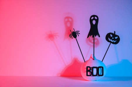 Halloween home decorations. Painted white pumpkin and black scary Halloween puppets on sticks, illuminated with neon light. Copy space