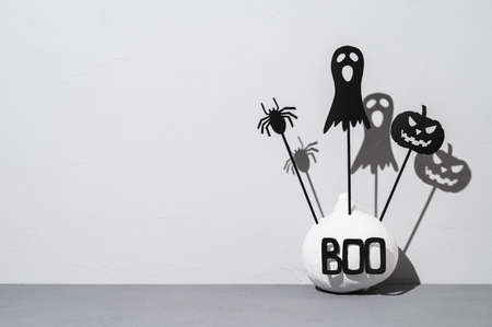 Halloween home decorations. Painted white pumpkin and black scary Halloween shadow puppets on sticks on a light gray background. Copy space