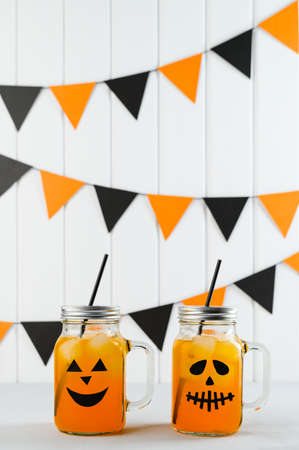 Halloween pumpkin iced mocktails in glass jars decorated with scary faces on a white table. DIY Halloween Party decoration on the wall. Party cocktails. Vertical orientation Banco de Imagens