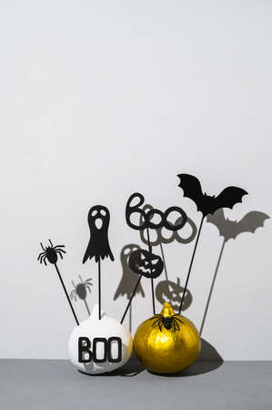 Halloween home decorations. Painted white and gold pumpkins with scary black Halloween objects with shadows on a gray background. Copy space, vertical orientation. Banco de Imagens