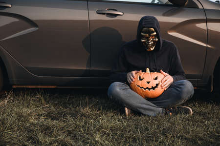 An unrecognizable adult man wearing a skull mask sits near a car on the grass and holds a carved pumpkin for Halloween, outdoors. Copy space. Daytime
