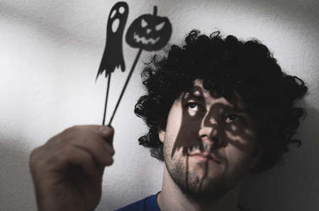 Portrait of an adult man in a black wig with shadows of Halloween pumpkin and a ghost on his eyes. Creates creepy puppet shadows.