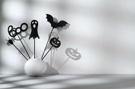 Halloween home decorations. Painted white pumpkin and black Halloween frightening puppets on sticks on a light gray background. Abstract shadow. Copy space