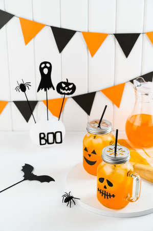 Halloween pumpkin iced mocktails in glass jars decorated with scary faces on a white table. DIY Halloween Party decoration on the wall. Party cocktails. Vertical orientation, View from above Banco de Imagens