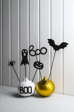 Halloween home decorations. Painted white and gold pumpkins with scary black Halloween objects on a white wooden wall background. Copy space, vertical orientation.