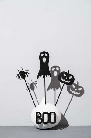 Halloween home decorations. Painted white pumpkin and black scary Halloween shadow puppets on sticks on a light gray background. Copy space, vertical orientation. Banco de Imagens