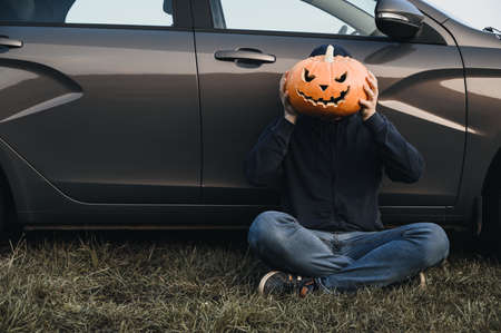 An unrecognizable adult man sits near a car on the grass and holds in front of his face a carved pumpkin for Halloween, outdoors. Copy space. Faceless concept Banco de Imagens