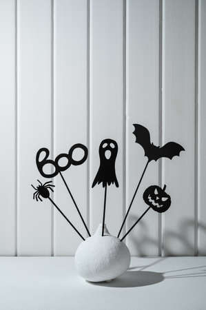 Halloween home decorations. Painted white pumpkin and black Halloween scary shadow puppets on sticks against a white wooden wall. Copy space, vertical orientation. Banco de Imagens