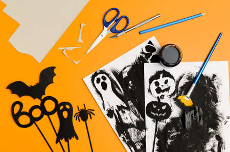 Preparing for Halloween. Handmade crafts. Top view of paper decorations for Halloween party on orange background. layout.