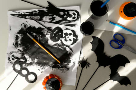 Preparing for Halloween. Handmade crafts. Top view of making paper decorations for Halloween party on white table. Flat lay Banco de Imagens