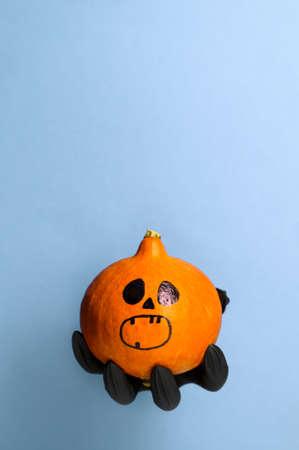 Creepy Black Hand holds a Halloween pumpkin on a pastel blue background. Halloween symbol. Copy space, vertical orientation