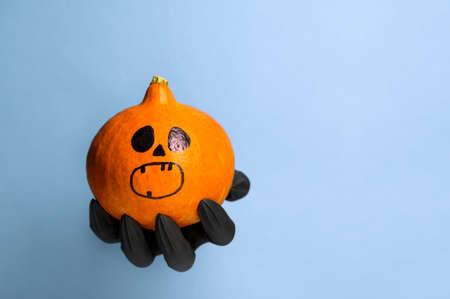 Creepy Black Hand holds a Halloween pumpkin on a pastel blue background. Halloween symbol. Copy space Banco de Imagens