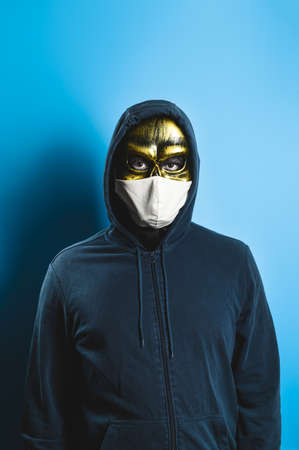 Era Covid. New normal concept. Portrait of a man in a skull mask and a protective medical mask on a blue background. Looking at the camera. Halloween party costume.