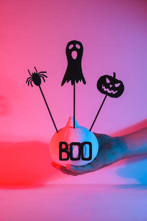 Halloween home decorations. A human hand holds a painted white pumpkin and black scary Halloween puppets on sticks, illuminated by neon light. vertical orientation. Banco de Imagens
