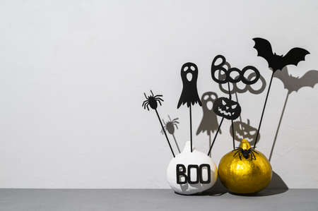 Halloween home decorations. Painted white and gold pumpkins with scary black Halloween objects with shadows on a gray background. Copy space
