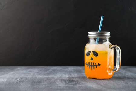 Iced pumpkin cocktail in glass jar decorated with scary face on the chalkboard, black background. Halloween Party mocktail. Copy space
