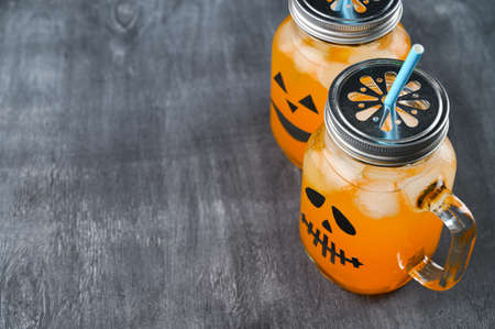 Iced pumpkin cocktails in glass jars decorated with scary faces on the chalkboard. Halloween Party mocktails. Copy space Banco de Imagens