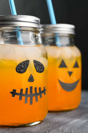 Iced pumpkin cocktails in glass jars decorated with scary faces on the chalkboard, black background. Halloween Party mocktails. Vertical orientation Banco de Imagens