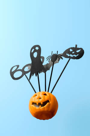 Halloween decorations. Bottom view Halloween party accessories and Jack-O-lantern pumpkin on pastel blue background. Copy space. Minimal style. Vertical orientation Banco de Imagens