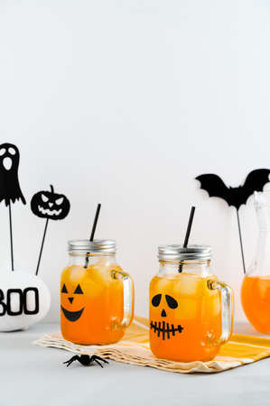Iced pumpkin cocktails in glass jars decorated with scary faces on a white table. DIY Halloween Party decoration. Halloween mocktails. Vertical orientation