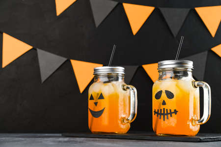 Halloween pumpkin iced mocktails in glass jars decorated with scary faces on a dark table. DIY Halloween Party decoration on black wall. Party cocktails.
