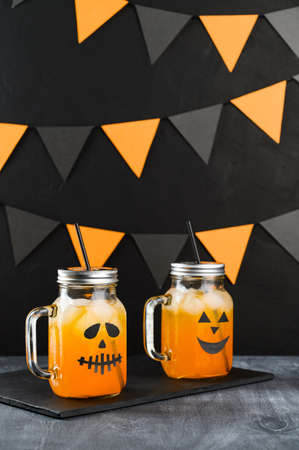 Iced pumpkin cocktails in glass jars decorated with scary faces on a dark table. DIY Halloween Party decoration on black wall. Halloween mocktails. Vertical orientation Banco de Imagens