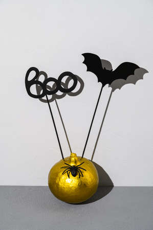 Halloween decorations. Painted golden pumpkin with scary black Halloween objects with shadows on a gray background. Copy space, vertical orientation. Banco de Imagens