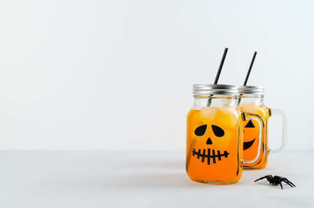 Iced pumpkin cocktails in glass jars decorated with scary faces on the gray table, white background. Halloween Party mocktails. Copy space Banco de Imagens