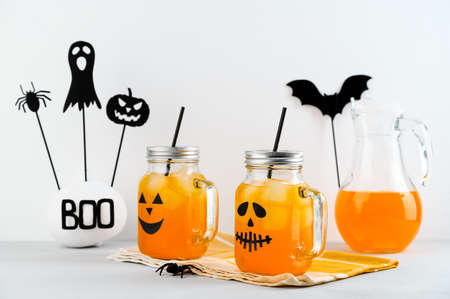 Iced pumpkin cocktails in glass jars decorated with scary faces on a white table. DIY Halloween Party decoration. Halloween mocktails