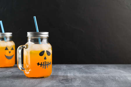 Iced pumpkin cocktails in glass jars decorated with scary faces on the chalkboard, black background. Halloween Party mocktails. Copy space
