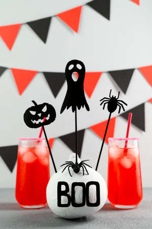 Iced pumpkin cocktails in glasses decorated with scary faces on a gray table. DIY Halloween Party decoration on the wall. Halloween mocktails. Vertical orientation Banco de Imagens