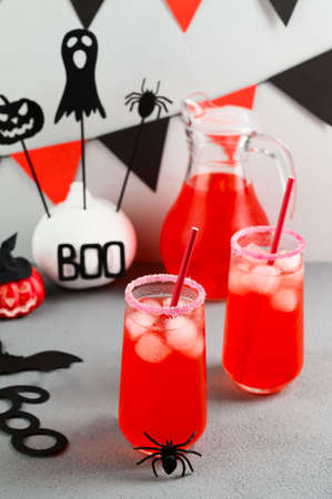 Iced pumpkin cocktails in glasses decorated with scary faces on a gray table. DIY Halloween Party decoration on the wall. Halloween mocktails. Vertical orientation, View from above Banco de Imagens