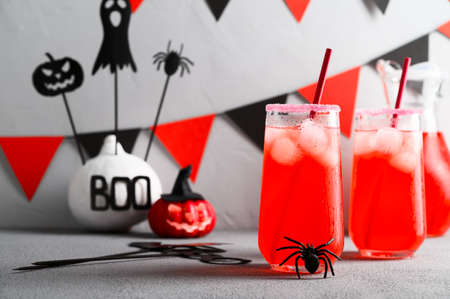 Iced pumpkin cocktails in glasses decorated with scary faces on a gray table. DIY Halloween Party decoration on the wall. Halloween mocktails.