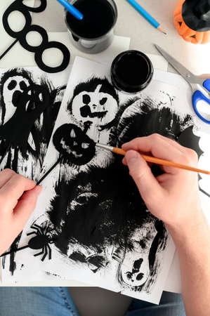 Preparing for Halloween. Handmade crafts. Top view of making paper decorations for Halloween party on white table. A male hand paints a paper pumpkin black. Flat lay Banco de Imagens