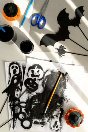 Preparing for Halloween. Handmade crafts. Top view of making paper decorations for Halloween party on white table. Flat lay, vertical orientation Banco de Imagens