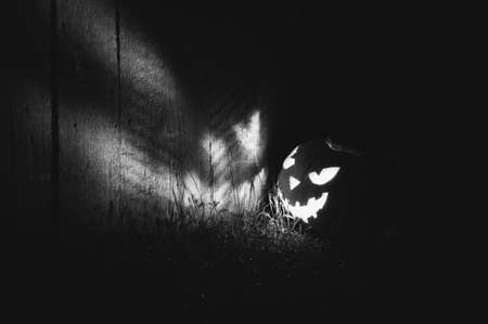 Halloween pumpkin lights up a wooden wall at night outside. Glowing face Jack-O-Lantern pumpkin on the wall. Black and white photography. Copy space.