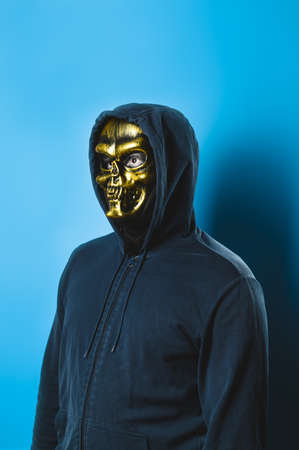 Portrait of a man in a skull mask with a hood on a blue background. Halloween party costume. Vertical orientation