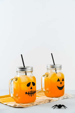 Iced pumpkin cocktails in glass jars decorated with scary faces on the gray table, white background. Halloween Party mocktails. Vertical orientation, copy space