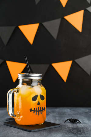 Iced pumpkin cocktail in glass jar decorated with scary face on a dark table. DIY Halloween Party decoration on black wall. Halloween mocktail. Vertical orientation Banco de Imagens