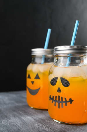 Iced pumpkin cocktails in glass jars decorated with scary faces on the chalkboard, black background. Halloween Party mocktails. Vertical orientation, copy space Banco de Imagens