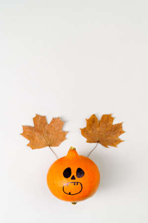 Top view of Halloween pumpkin with painted face and horns from autumn leaves on gray background. Vertical Orientation, Copy Space, Flat Lay. Banco de Imagens