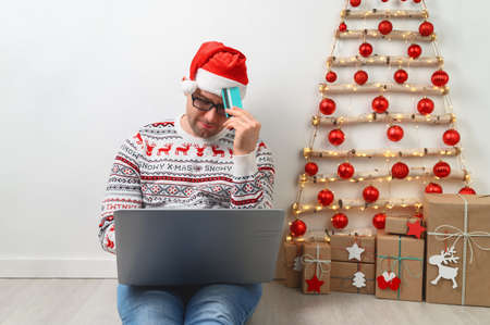 Christmas shopping online. Adult man sits on the floor near the Christmas tree, holds credit card, buys gifts online, using laptop. Man in sweater is shopping online during Christmas and winter sales