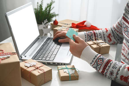 Christmas shopping online. Unrecognizable Man Hands holding Credit Card buying presents by using laptop. The man wearing a sweater shopping online at the home office