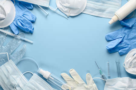 Used disposable medical face masks, latex gloves, syringes, test tubes on pastel blue background. Problem of environmental pollution during pandemic of coronavirus COVID-19. Flat lay, place for text Stock Photo