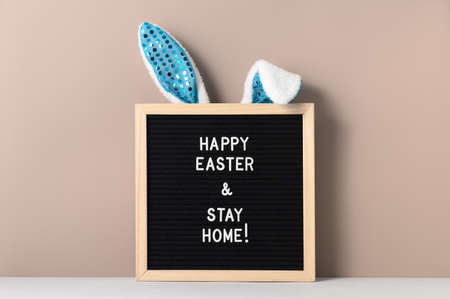 Easter holiday concept 2021. Cyan bunny ears and black felt letter board with a slogan - Happy Easter and Stay at Home on a beige background. Vertical orientation