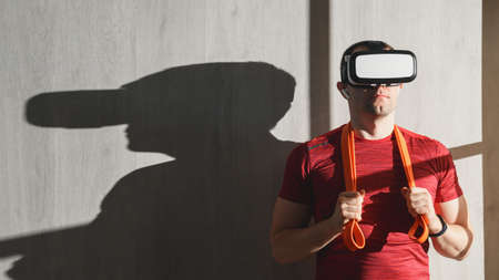 Fitness, workout and VR technology. Portrait Caucasian young adult man in a red t-shirt with an expander on the shoulders, wearing virtual reality glasses. Indoors, copy space