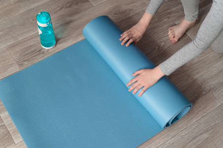 Teenage girl doing fitness exercise, practicing yoga at home. Healthy lifestyle concept. She spreads the yoga mat. Workout at home. Home interior, daytime.