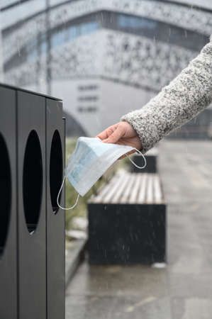 Female hand throws used medical mask into garbage can in the urban street.
